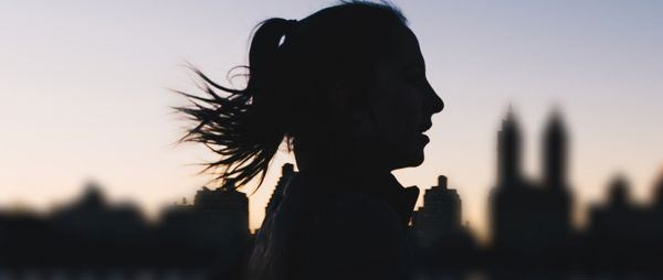 Woman running in the city at dusk